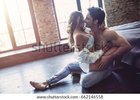 Passionate couple in bedroom is having sex on floor.