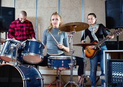 Passionate emotional happy smiling female drummer with her bandmates practicing in rehearsal room