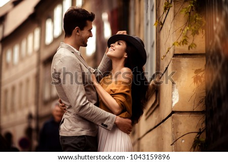 Passionate gorgeous young couple embrace each other while walk across ancient city. Cheerful elegant cute female model wears stylish hat, looks with cheerful expression in her boyfriend s eyes.
