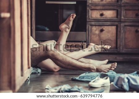 Passionate love. View of feet of a young couple that lying on the floor in the kitchen at home.