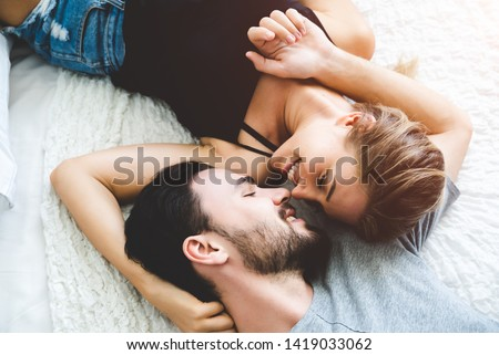 Passionate woman gently kissing man on with romantic kiss.desire lying on bed, young tender lover enjoys touching soft skin of sensual sexy lady moaning having sex. #1419033062