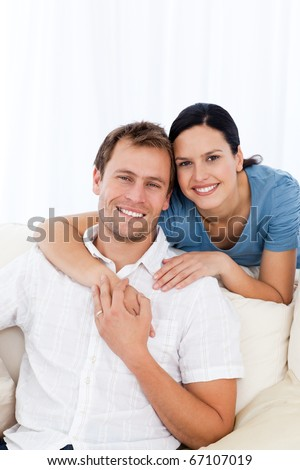 Passionate woman hugging her boyfriend while relaxing on the sofa at home