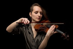 Passionate woman violinist playing classical music on a handcrafted antique Baroque violin in a frontal portrait over a black background