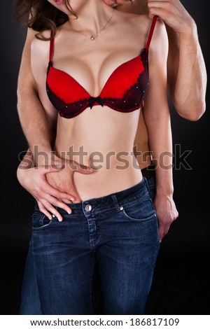 Passionate young man inserting hand in woman\'s jeans while kissing her on neck isolated over black background