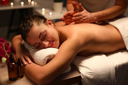 Passive girl lye on massage table covered with white towel and enjoy. Man do back massage with his hand. Candle burn in background.