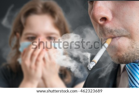 Passive smoking concept. Man is smoking cigarette and woman is covering her face. A lot of smoke around.
