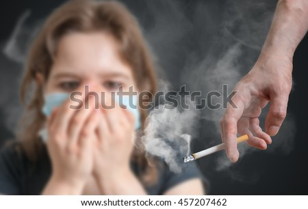 Passive smoking concept. Woman is covering her face from cigarette smoke.
