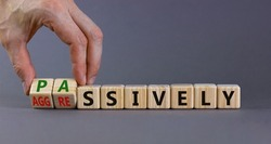 Passively or aggressively symbol. Businessman turns cubes and changes the word passively to aggressively. Psychological and passively or aggressively concept. Beautiful grey background, copy space.