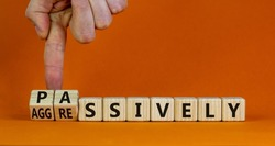 Passively or aggressively symbol. Businessman turns cubes and changes the word passively to aggressively. Psychological and passively or aggressively concept. Beautiful orange background, copy space.