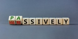 Passively or aggressively symbol. Turned wooden cubes and changed the word 'passively' to 'aggressively'. Psychological and passively or aggressively concept. Beautiful grey background, copy space.