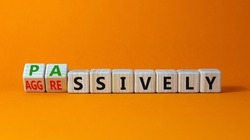 Passively or aggressively symbol. Turned wooden cubes and changed the word passively to aggressively. Psychological and passively or aggressively concept. Beautiful orange background, copy space.