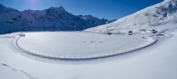 Passo del Tonale, Italy. Artificial water catchment reservoir for snow skiing slopes. Winter time. Frozen lake