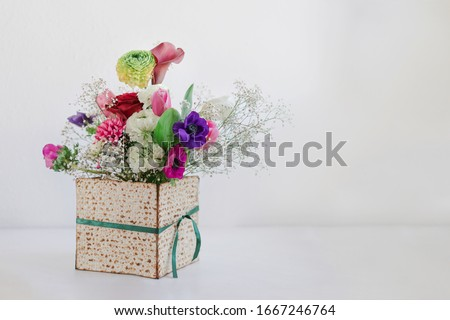 Passover background with spring flower bouquet in matza box with copy space. Happy Passover Spring Festive season greeting card. Jewish holidays arrangement