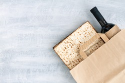 Passover grocery shopping composition with a matzah or matza and red kosher in a paper shopping bag. Top view or overhead view composition with copy space