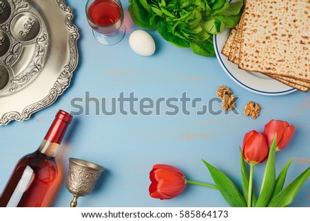 Passover holiday concept seder plate, matzoh, tulip flowers and wine bottle on wooden background. Top view from above