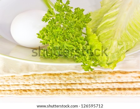Passover seder plate and matza. Close up of three covered matzas under a ceramic seder plate with hard boiled egg, parsley, and romaine lettuce leaf.