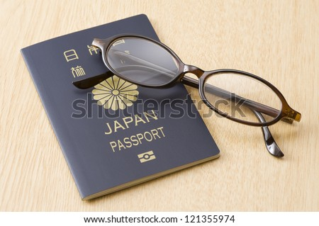 passport and brown frame eyeglasses on wooden table