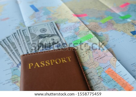 Passport and US dollar on a world map paper as pastel tones with stickers or post it reflecting light on a lot of countries to mark business destinations, travel, investment or study in past to future
