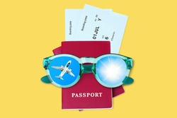 Passport, boarding pass, flight ticket, sunglasses, airplane, shiny sun in blue sky top view close up on yellow background, summer holidays, vacation concept, travel banner, international tourism