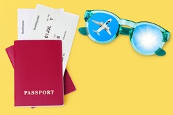 Passport, boarding pass, flight ticket, sunglasses, airplane, shiny sun in blue sky top view close up on yellow background, summer holidays, vacation, travel banner, international tourism, copy space