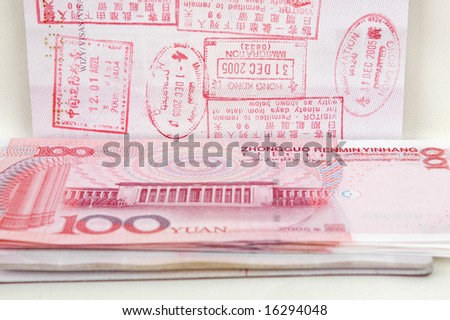 Passport full of stamps from China and Hongkong borders together with Chinese money, RMB banknotes.