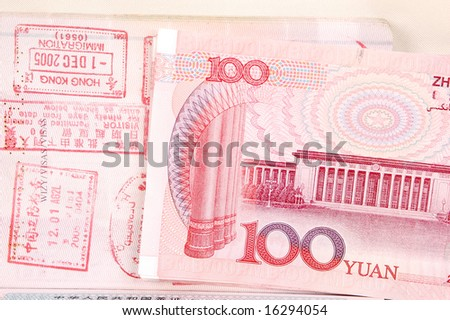 Passport full of stamps from China and Hongkong borders together with Chinese money, RMB banknotes. - stock photo