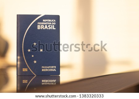Passport of brazil with sunset to the background - passport of brazil in foot with space for text or legend - to travel abroad is necessary passport