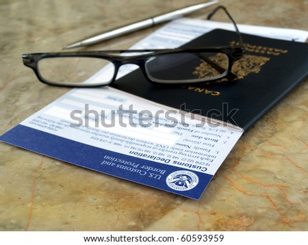 passport on U.S. customs and border form with glasses and pen