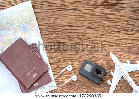 Passport with a map on old wooden background.Travel planning.Top view of traveler accessories with a camera, plane on world map.Preparation for travel.Traveling Journey Vacation Holiday concept.