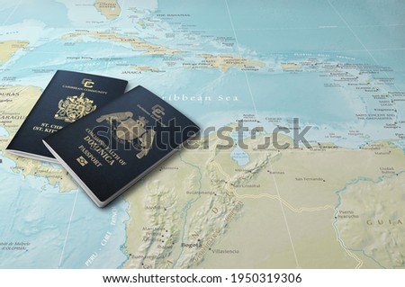 Passports of two Caribbean states, Saint Kitts and Nevis and Dominica on a map of the Caribbean Sea Stockfoto ©