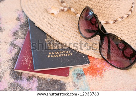 passports on beach towel and sand with hat and sunglasses depicting summer or tropical travel