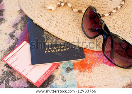 passports on beach towel and sand with hat and sunglasses depicting summer or tropical travel with blank boarding pass