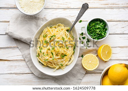Pasta al Limone, delicious Italian meal, spaghetti with Parmesan, butter and lemon sauce, topped with fresh grated zest and cheese on rustic wooden background