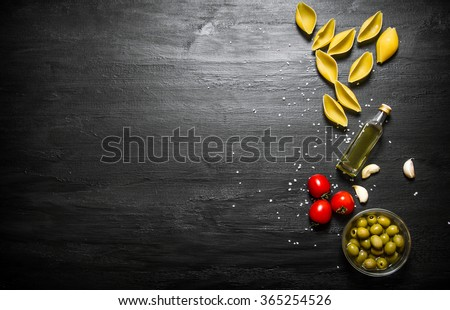 Pasta background. Dry pasta with olive oil and tomatoes. On a black wooden background. Free space for text . Top view