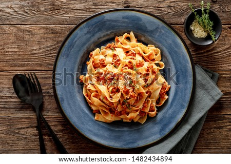 Pasta bolognese. Traditional italian dish of pasta with tomato and meat mince sauce served in a plate with parmesan cheese and thyme, top view