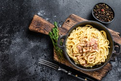 Pasta Carbonara with bacon and parmesan in a pan. Black background. top view. Copy space