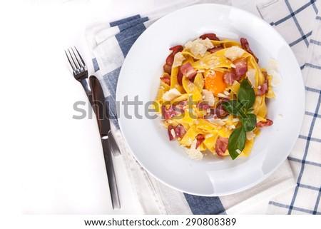 Pasta carbonara with tagliatelle spaghetti, egg yolk, bacon and basil ...