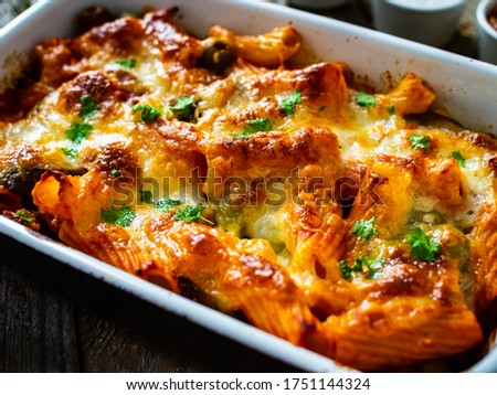 Photo of  Pasta casserole with minced meat, mozzarella cheese and vegetables on wooden table