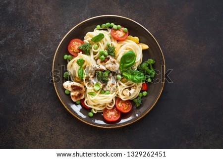 Pasta Chicken Primavera. Spaghetti pasta with grilled chicken meat, vegetables and basil, top view, copy space. Seasonal pasta primavera recipe. Foto stock ©