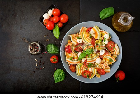Pasta colored farfalle salad with tomatoes, mozzarella and basil. Flat lay. Top view.