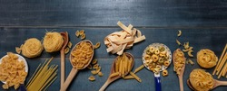 Pasta cooking concept. Raw pasta various shapes and spoons on blue wooden table background, top view
