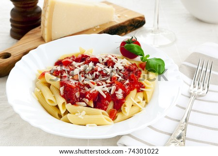 pasta dish with penne, tomato sauce, grated parmesan and basil, cheese and pepper mill in background