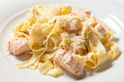 Pasta fettuccine alfredo with chicken, parmesan and parsley on white plate. Italian cuisine. Close up