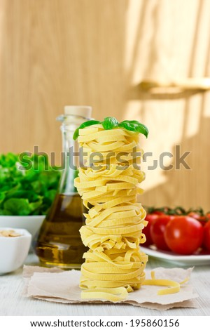 Pasta fettuccine on wooden background with different ingredients, selective focus