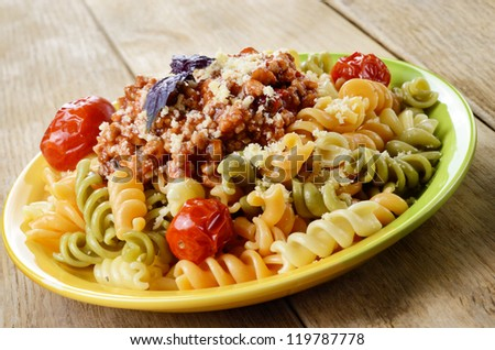 Pasta fusilli with bolognese tomato beef sauce and dried tomatoes on the kitchen table