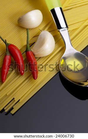 pasta garlic olive oil and red chili pepper ove black reflective surface
