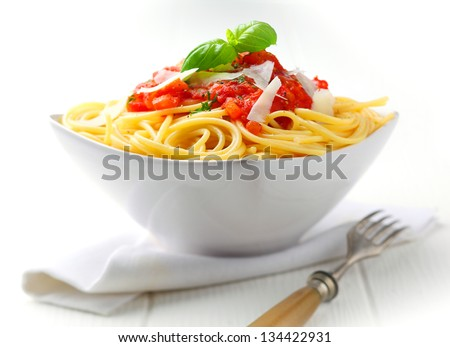 Pasta in a white bowl with tomato sauce and fresh basil set against a white napkin on a white table.