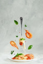 Pasta linguine with prawns and fork flying over the dish. Creative still life. Italian food.