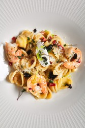 Pasta Orecchiette with Shellfish Seafood and Parmesan Cheese. Dark stone table with textile napkin