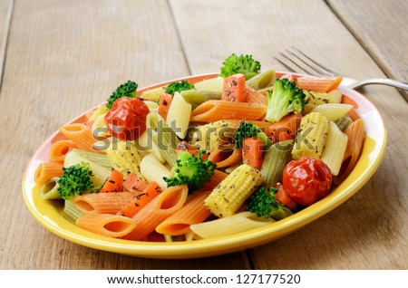 Pasta penne salad with broccoli, carrot, corn, and tomatoes on the wooden table